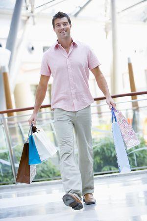 low angle views: El hombre con bolsas de la compra en un centro comercial