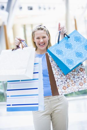 looking towards camera: Woman with shopping bags at a shopping mall Stock Photo