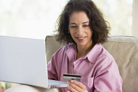 online shoppping: Woman with a laptop computer making an online purchase with credit card