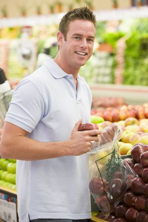 produce sections: Man shopping for apples at a grocery store