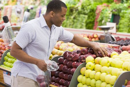 shoppers: Man shopping for apples at a grocery store