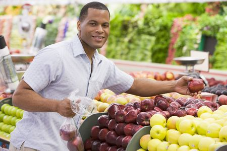 store interior: Man shopping for apples at a grocery store