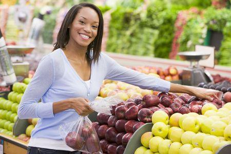 consommateurs: Femme de shopping pour les pommes � l'�picerie