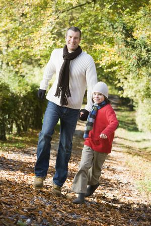Man and young boy walking outdoors in park and smiling photo