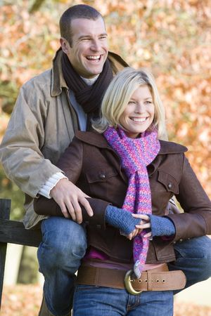 Couple outdoors in park by fence smiling (selective focus) Stock Photo - 3217951