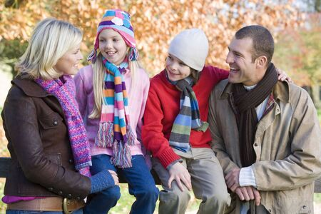 Family outdoors in park smiling (selective focus) photo