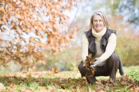 caucasoid race: Woman outdoors holding leaves and smiling (selective focus) Stock Photo