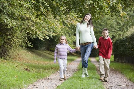 caucasoid race: Mother and two children walking on path outdoors smiling (selective focus)