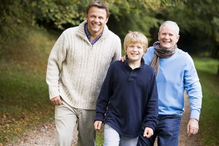 sons and grandsons: Two men and young boy walking on path outdoors smiling (selective focus)