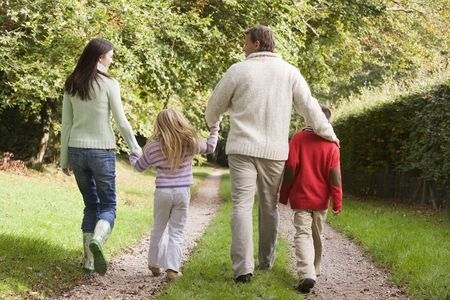 Family outdoors walking on path holding hands (selective focus) Stock Photo - 3207794