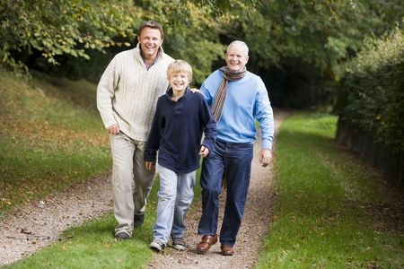 Two men and young boy walking on path outdoors smiling (selective focus) Stock Photo - 3217724