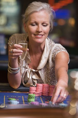 gamers: Woman in casino playing roulette and smiling (selective focus)