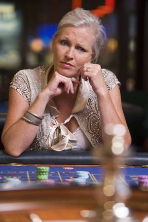 Woman in casino playing roulette and thinking (selective focus) photo