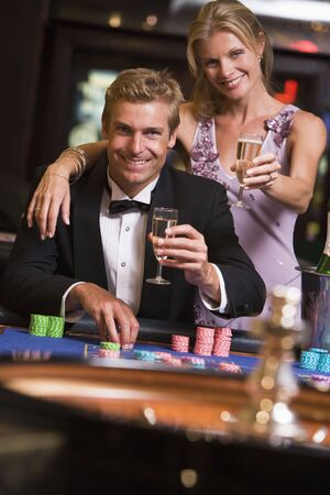 gambling parlour: Couple in casino at roulette table holding up champagne and smiling (selective focus) Stock Photo