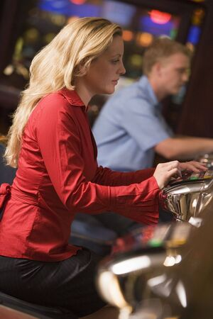 caucasoid race: Woman in casino playing slot machine with people in background (selective focus) Stock Photo