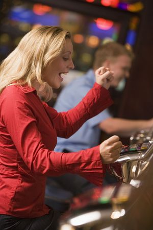 gambling parlour: Woman in casino excited playing slot machine with people in background (selective focus) Stock Photo