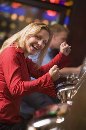 gambling parlors: Woman in casino excited playing slot machine with people in background (selective focus) Stock Photo