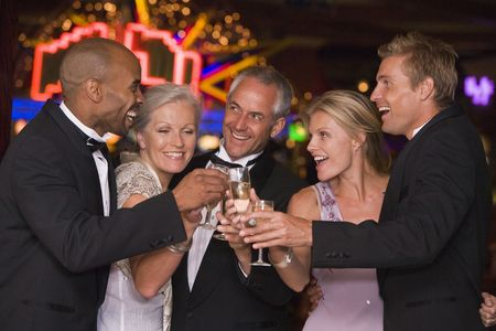 gambling parlour: Five people in casino toasting champagne smiling (selective focus)