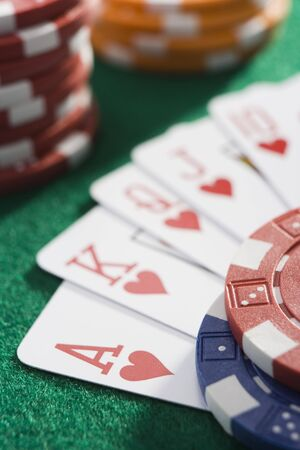 gambling parlour: Playing cards making royal flush in hearts by poker chips (close upselective focus)