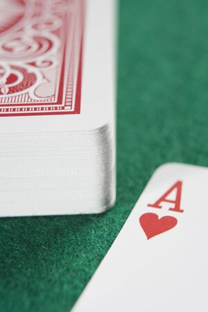 gambling parlour: Deck of cards on a poker table with ace of hearts showing (close upselective focus)