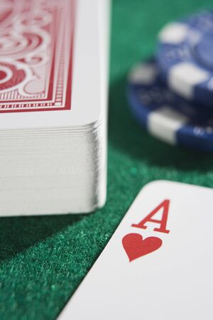 parlours: Deck of cards and poker chips on a poker table with ace of hearts showing (close upselective focus) Editorial