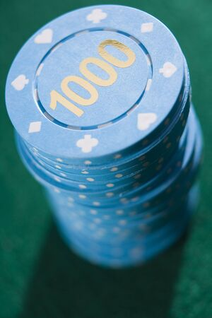 gambling parlors: Poker chips piled on a poker table (close updepth of field)