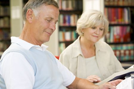 Man and woman in library reading (selective focus) photo