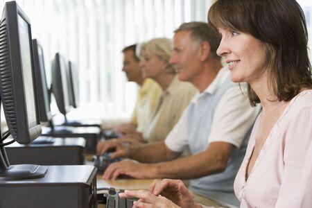 четыре человека: Four people sitting at computer terminals (depth of fieldhigh key)