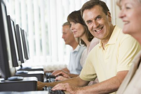 boomers: Four people sitting at computer terminals (selective focushigh key)
