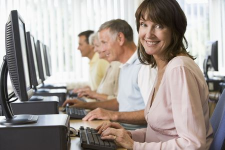 Four people sitting at computer terminals (depth of field/high key) Stock Photo - 4498670
