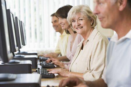 Cuatro personas sentadas en terminales de computadora (atención selectiva / alto clave)