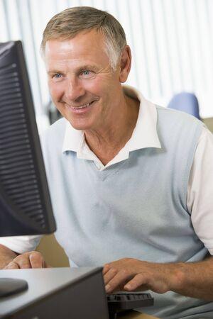 computer centres: Man sitting at a computer terminal typing (high key)