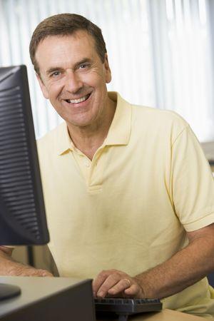 Man sitting at a computer terminal typing (high key)