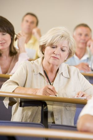 frontal views: Woman sitting in adult classroom taking notes with students in background (selective focus)