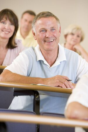 Man sitting in adult classroom laughing with students in background (selective focus) photo
