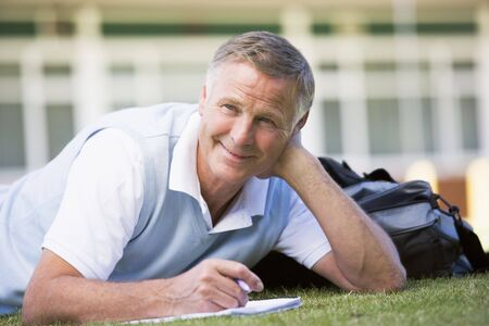 Adult student lying on lawn of school with notebook photo