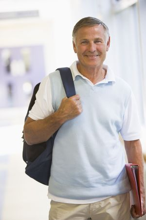 Man standing in corridor with backpack (high key) photo