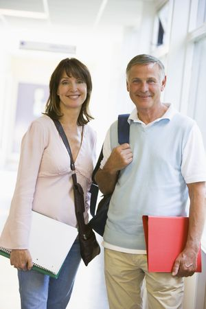 Man and woman standing in corridor with books (high key)