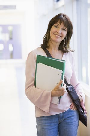 Woman standing in corridor with books (high key)