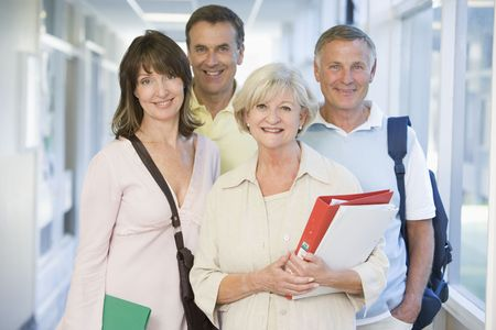 Four people standing in corridor with books (high key) Stock Photo