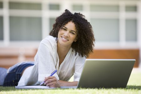 Woman lying on lawn of school with laptop photo