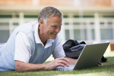 uses a computer: Man lying on lawn of school with laptop