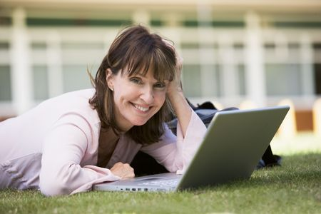 peacefulness: Woman lying on lawn of school with laptop
