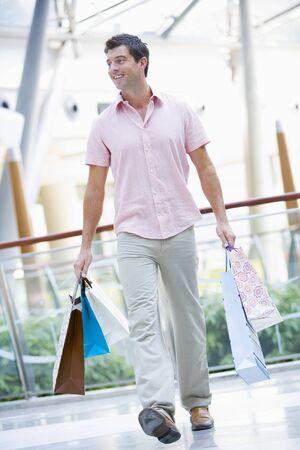 low angle views: El hombre con bolsas de compras en un centro comercial