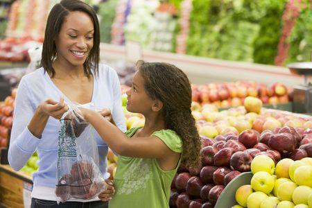La mujer y su hija de compras para las manzanas en una tienda de comestibles