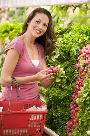 produce sections: Woman shopping for beets at a grocery store