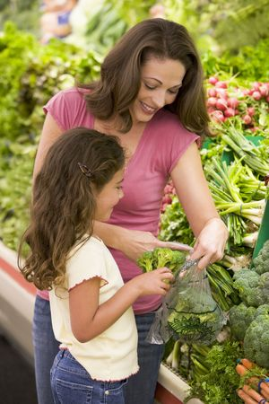 Mother and daughter shopping for broccoli at a grocery store photo