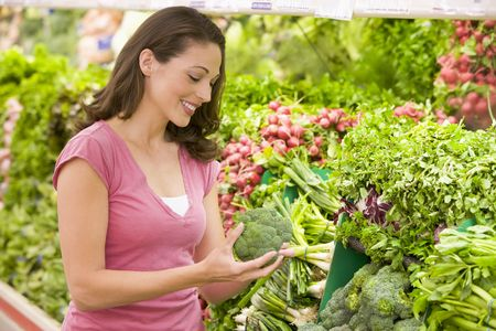 selections: Woman shopping for broccoli at a grocery store
