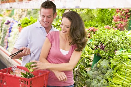 Young couple shopping for broccoli at a grocery store photo