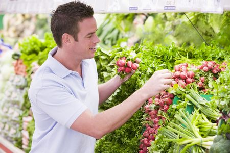 Man shopping for beets at a grocery store photo